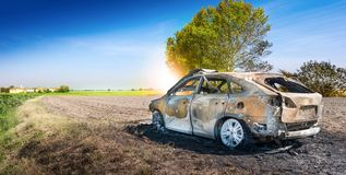 Verlassenes gebranntes Auto an lokalisiertem Feld Stockbild