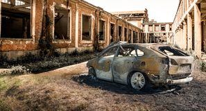 Verlassenes gebranntes Auto an lokalisierter Ruine Stockfotografie