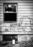 Verlassenes Haus mit unterbrochenem Fenster und Graffiti. Stockfotos