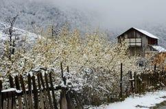 Verlassenes Holzhaus mit altem gebrochenem Zaun im Winter, Armenien Stockbild