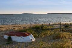 Verlassenes kleines Fischerboot auf Strand am Sonnenuntergang Lizenzfreie Stockfotos