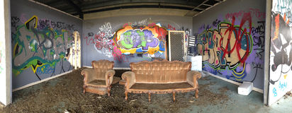 Verlassenes städtisches Gebäude mit Graffiti und absichtlichem Schaden Panor Stockfoto