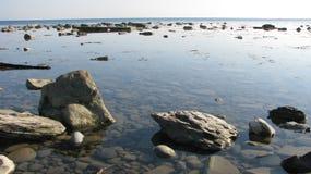 Verlassenes Ufer des Meeres, voll von der Ruhe, Felsen im Wasser Stockfotos