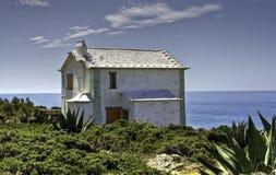 Verlassenes weißes Gebäude durch das Meer Stockbild