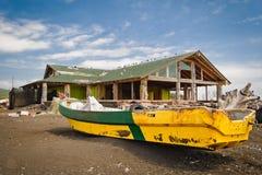 Verlaten boot en huis bij het strand Stock Foto