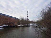 Verlaten de baksteen verliet onbeheerde installatie met een steenpijp op de rivier, tegen de blauwe hemel en de wolken in de wint stock fotografie