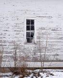 Verlaten de bouwvenster met doorstaan hout in de winter Stock Foto's