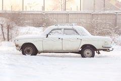Verlaten die auto met sneeuw in de winter bij zonsondergang, warme tonen, zijaanzicht wordt behandeld Het roesten, recycling, met stock afbeelding