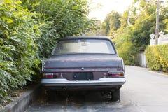 Verlaten die auto naast de boom wordt geparkeerd Stock Foto