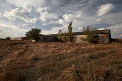 Verlaten die landbouwbedrijf buiten, met gras wordt overwoekerd, de vroege herfst Royalty-vrije Stock Afbeeldingen
