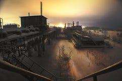Verlaten fabriek, in sneeuwval, nacht industrieel landschap stock foto