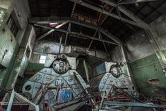 Verlaten fabriekshangaar met reuze antieke boilers stock afbeelding