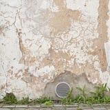 Verlaten gebarsten gipspleistermuur met ventilatietraliewerk Royalty-vrije Stock Fotografie