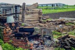 Verlaten geruïneerd oud huis, hut In de middentribunes een fornuis Het gevallen dak Stock Foto's