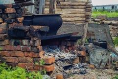 Verlaten geruïneerd oud huis, hut In de middentribunes een fornuis Het gevallen dak Royalty-vrije Stock Afbeelding