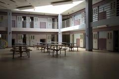 Verlaten gevangenis gemeenschappelijke ruimte in celblok stock foto