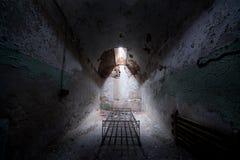 Verlaten gevangeniscel met een oud bedkader Stock Foto
