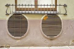 Verlaten grunge gebarsten gipspleistermuur met de gaten van het ventilatietraliewerk Stock Afbeeldingen