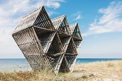 Verlaten houten geometrisch beeldhouwwerk op wild strand Royalty-vrije Stock Foto's
