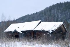 Verlaten houten hut in het de winterlandschap stock foto