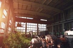 Verlaten industrieel griezelig pakhuis binnen de oude donkere bouw van de grungefabriek met staal roestig materiaal bij zonlicht Royalty-vrije Stock Afbeeldingen