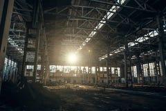 Verlaten industrieel griezelig pakhuis binnen de oude donkere bouw van de grungefabriek in zonlicht Stock Fotografie