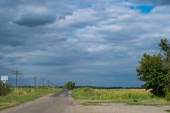 Verlaten landweg door een gebied en een bewolkte hemel stock afbeelding