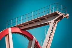 Verlaten metaal het duiken structuur Iconische industriële en sportenarchitectuur, witte en rode staalelementen op een diepe blau stock fotografie
