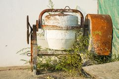 Verlaten mobiele concrete mixer in tuin stock afbeeldingen