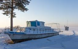 Verlaten motorboot op de sneeuwkust van het Ob-reservoir royalty-vrije stock foto