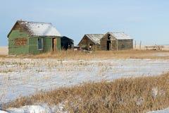 Verlaten oud loodsen en landbouwwerktuig in de winter Stock Afbeelding