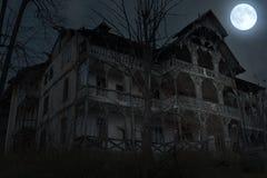 Verlaten oud spookhuis met donkere verschrikkingsatmosfeer in het maanlicht royalty-vrije stock foto