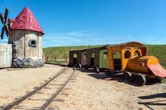 Verlaten oude modellen van houten trein en windmolen stock afbeeldingen