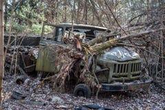 Verlaten ouderwetse militaire spoorverblijven in bos in de Uitsluitingsstreek van Tchernobyl De gebroken boom legt op zijn kap royalty-vrije stock afbeeldingen