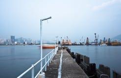 Verlaten pier bij een mistige overzees dichtbij een Nederlandse stad. Stock Foto's