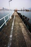Verlaten pier bij een mistige overzees dichtbij een Nederlandse stad. Royalty-vrije Stock Foto