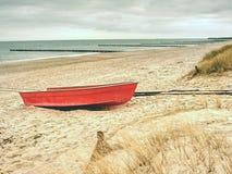 Verlaten rode peddelboot op zandig strand van overzees Vlotte waterspiegel Stock Afbeeldingen