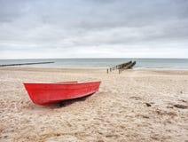 Verlaten rode peddelboot op zandig strand van overzees Vlotte waterspiegel Royalty-vrije Stock Fotografie