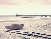 Verlaten rode peddelboot op zandig strand van overzees Vlotte waterspiegel Royalty-vrije Stock Foto