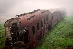 Verlaten roestende trein en lege die treinsporen in een mistige dag wordt gefotografeerd royalty-vrije stock afbeeldingen
