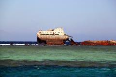 Verlaten roestig schip in blauwe overzeese golven Stock Afbeelding