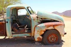 Verlaten roestige bestelwagenauto in woestijn, Afrika Stock Afbeelding