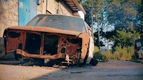 Verlaten roestige rode auto in de werf in de zomer stock videobeelden