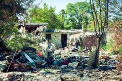 Verlaten ruïne van huis na granaatexplosie in overal het bombarderen van met overblijfselen de werf Stock Afbeelding
