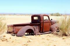 Verlaten rustieke bestelwagenauto in woestijn, Afrika Stock Foto