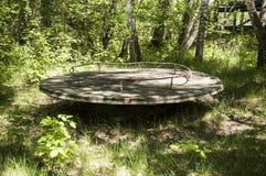 Verlaten speelplaats in bos Stock Fotografie