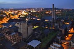 Verlaten staalfabriekenfabriek in dark met een glanzende stad op de achtergrond Stock Foto's