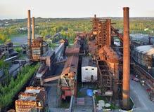 Verlaten staalfabriekenfabriek met bos op de achtergrond Stock Afbeelding