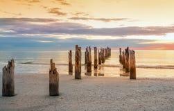 Verlaten strand en en de overblijfselen van de geruïneerde pijler in het water stock foto's