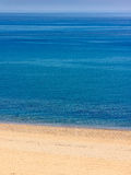 Verlaten strand met briljante blauwe overzees Royalty-vrije Stock Foto